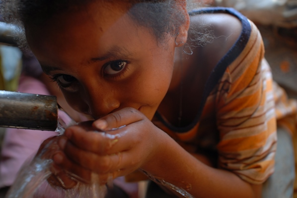 Child drinking from Fairtrade-funded protected spring, Haro, Ethiopia